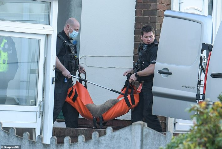 Pictured: Two officers carry the second presumably tranquillised dog in an orange bag towards an open van outside