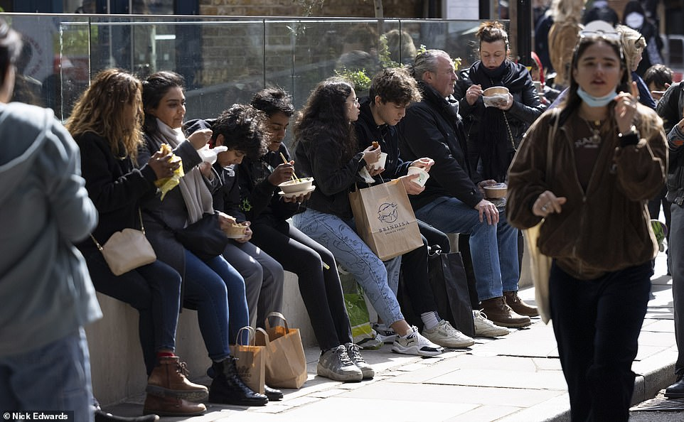 Friends gathered outside to sit down in London's Borough Market and enjoy some fish and chips at the start of the long weekend