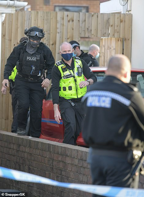 Pictured: Officers walk down the side of the house inRowley Regis
