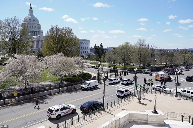 Police officers surround the scene after a car that crashed into a barrier on Capitol Hill on the Senate side of the U.S. Capitol in Washington, Friday, April 2, 2021