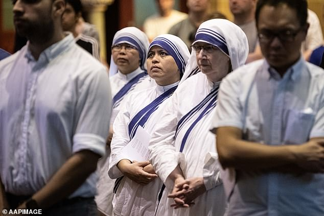 Members of the congregation at St Mary's Catherdral in Sydney on Friday (pictured)