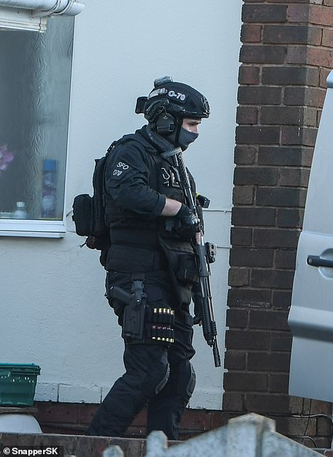 Pictured: An armed police officer is seen leading other officers out of the home of the woman to an open van