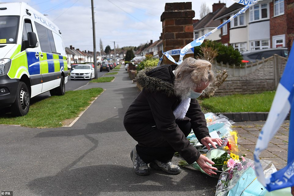A woman puts flowers down outside the house on Boundary Avenue in Rowley Regis, West Midlands, where a woman in her 80s died after being attacked by two escaped dogs
