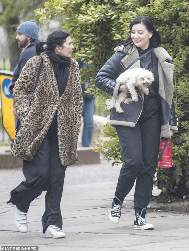 Beloved pet: She was joined by a friend who also wrapped up, wearing a long leopard print fur coat and wide legged black trousers as they walked with her dog
