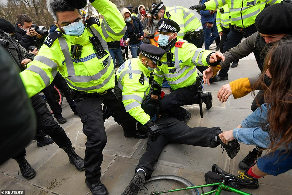 Police officers are seen restraining a demonstrator during a 'Kill the Bill' protest in central London this afternoon