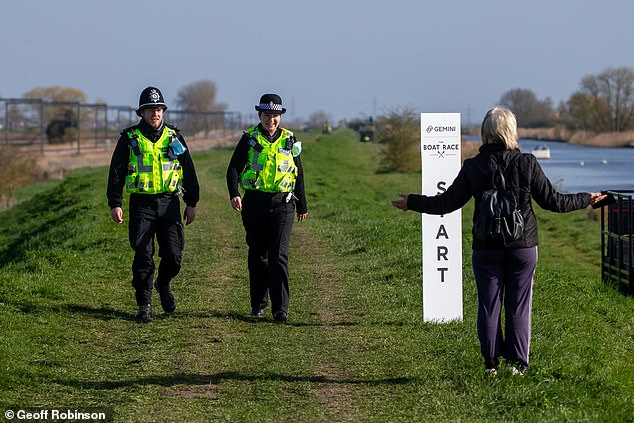 Police have warned people will be fined £200 for attempting to view the race from the riverbanks in Ely this weekend. Pictured: Police patrolling the river this morning