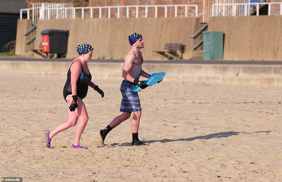 A couple are seen in their swimming gear after taking the plunge on Sandbanks beach for morning exercise