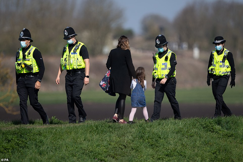 Police patrol the river bank before the Boat Race on the River Great Ouse near Ely in Cambridgeshire
