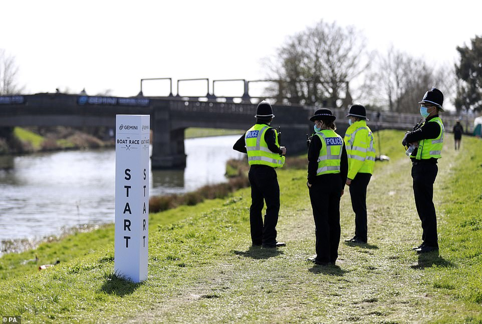 Police patrol the river banks ahead of the Boat Race on the River Great Ouse near Ely in Cambridgeshire