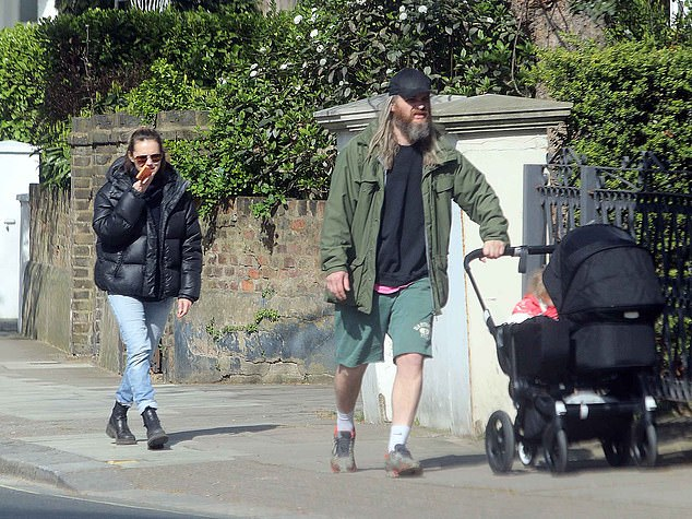 Casual: Sporting a baseball cap and a black sweater and green shorts, chiropractor Marius, 35, took steered their baby's pram through the streets as Frey rested on the edge