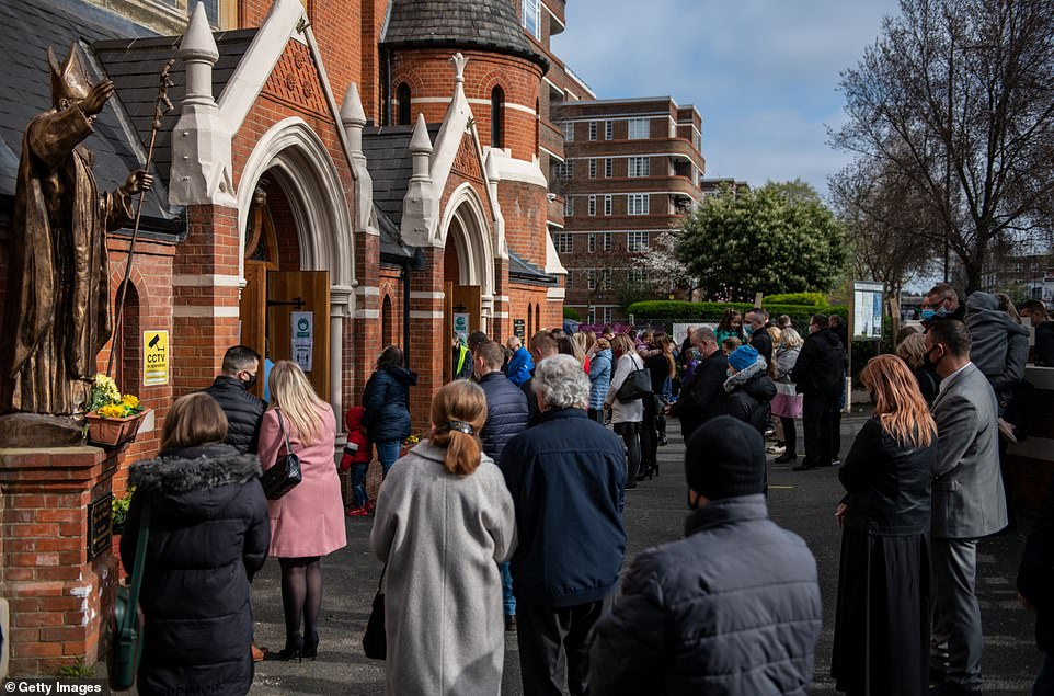 Christians stand outside during an Easter Sunday service due to lack of space indoors because of covid-19 social distancing guidelines