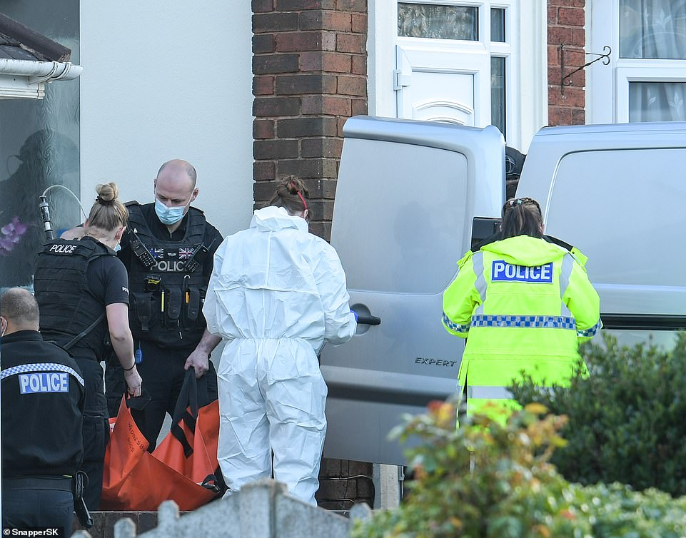 Armed police and forensic officers leave the house, two of whom are seen carrying the sedated body of a dog