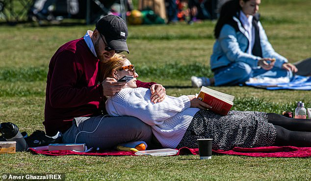 A couple relaxed together in Wimbledon Common in south London during the spring sunshine on the balmy Bank Holiday weekend