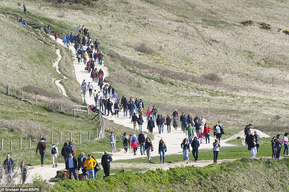Crowds are seen flowing the path to and from the beach in Durdle Door, Lulworth, Dorset on Easter Sunday