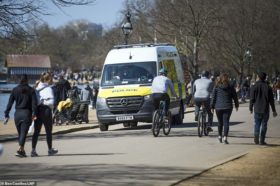 Police watch from their van in Hyde Park, which is full of people enjoying the Easter Sunday sun