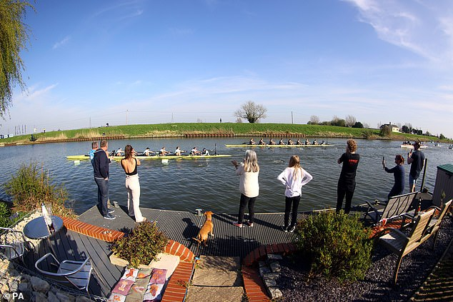 Spectators cheer on from the river bank as Cambridge lead Oxford in the 75th Women's Boat Race Boat Race