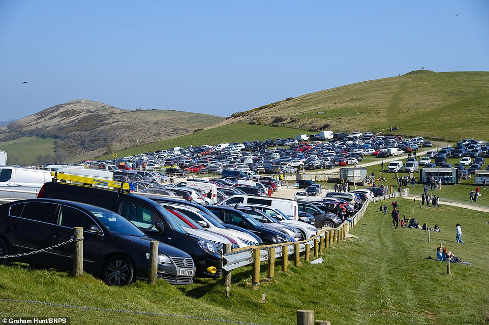 Visitors flock to Durdle Door on a day of warm sunshine during Easter Sunday. The main car park is packed with vehicles