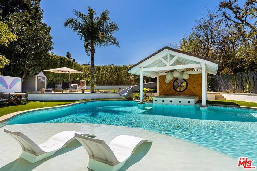 The backyard of the home includes a large swimming pool with water slide and a cabana
