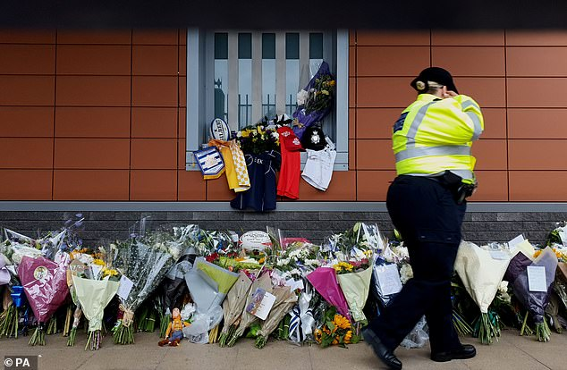Flowers are laid outside Croydon Custody Centre in south London after Sergeant Ratana was shot in the chest