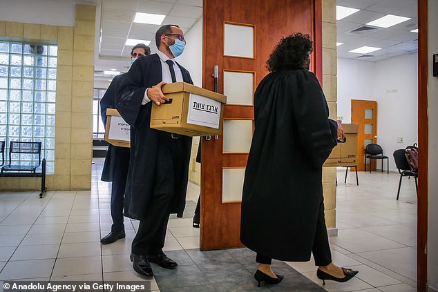 Prosecutors say Israel's longest-serving Prime Minister used his political influence as 'currency' to buy favours from media executives and wealth businessmen. Pictured:The court files are brought to the Jerusalem District Court ahead of the third hearing of Israeli Prime Minister Benjamin Netanyahu in East Jerusalem on April 5