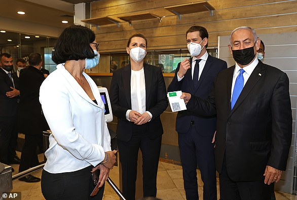 """Israeli Prime Minister Benjamin Netanyahu, right, holds a """"Green Pass,"""" for citizens vaccinated against COVID-19, as he visits a fitness gym with Austrian Chancellor Sebastian Kurz, second right"""