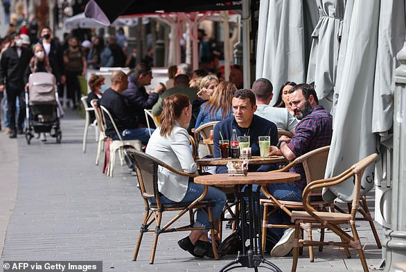 """People sit at cafe terraces in Jerusalem on March 9, 2021, after Israeli authorities reopened restaurants, bars and cafes to vaccinated """"green pass"""" holders"""