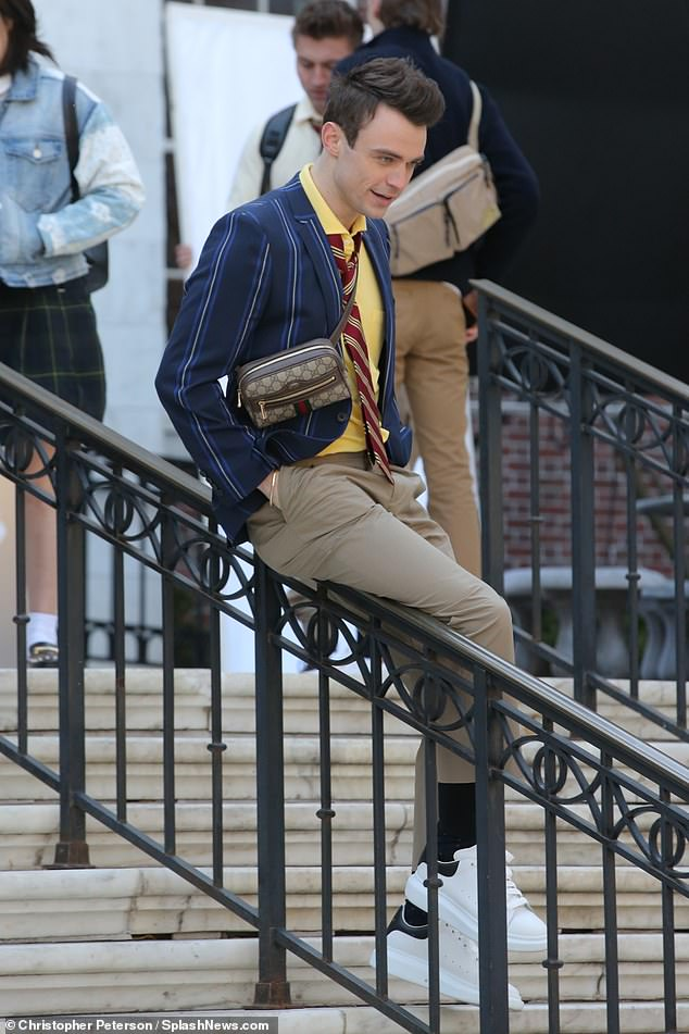 Gucci guy: Thomas Doherty donned a striped jacket, yellow shirt and red tie with a Gucci bag