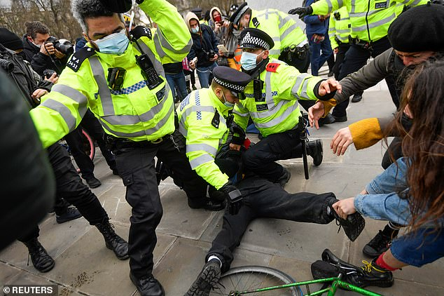 Police officers are seen restraining a demonstrator during a 'Kill the Bill' protest in London