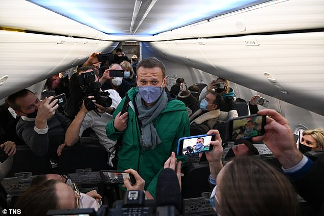 Navalny walks to take his seat in a Pobeda airlines plane heading to Moscow before take-off from Berlin Brandenburg Airport (BER) in Schoenefeld, southeast of Berlin, on January 17, 2021