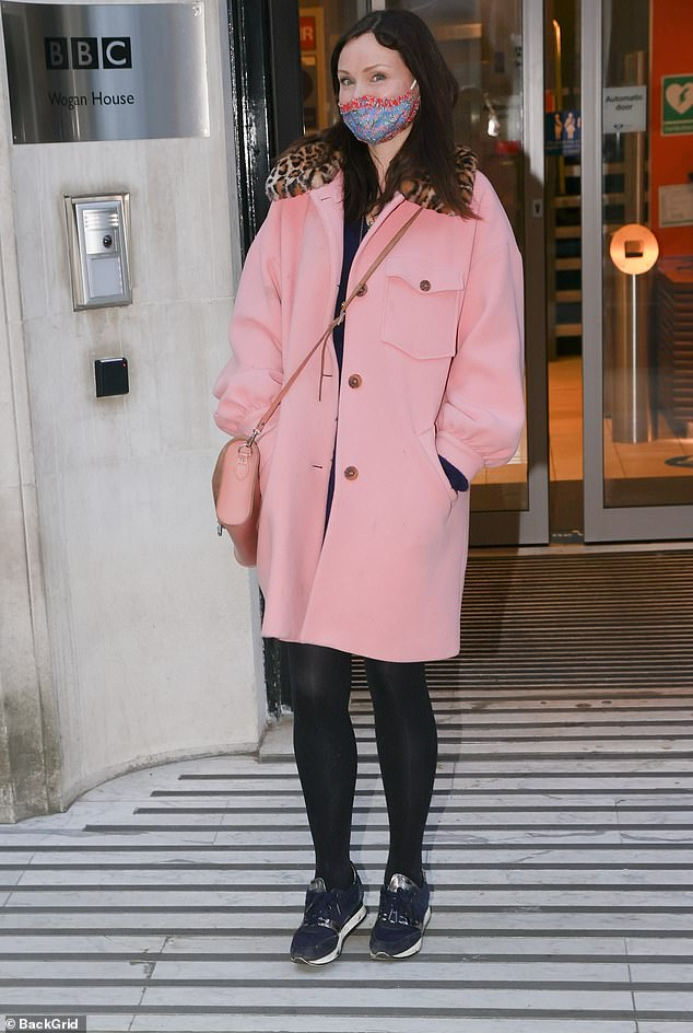Ready to go: The songstress paired the coat with black tights and practical trainers for her journey home and wore a pastel pink cross-body bag to carry her essentials
