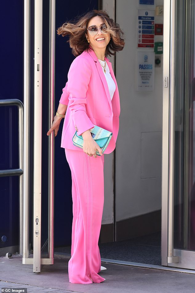 Radiant: She teamed the eye-popping tailoring with a white T-shirt and accessorised with a contrasting blue clutch bag