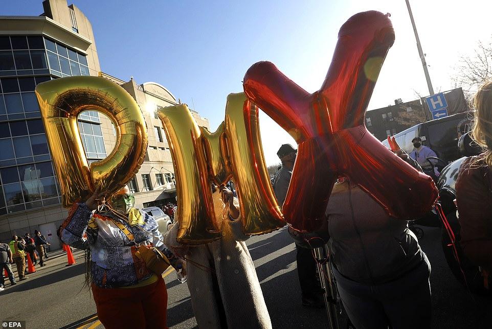 Disa tifozë mbajnë lart balonat 'DMX' gjatë vigjiljes së lutjes të hënën jashtë Spitalit White Plains në Nju Jork