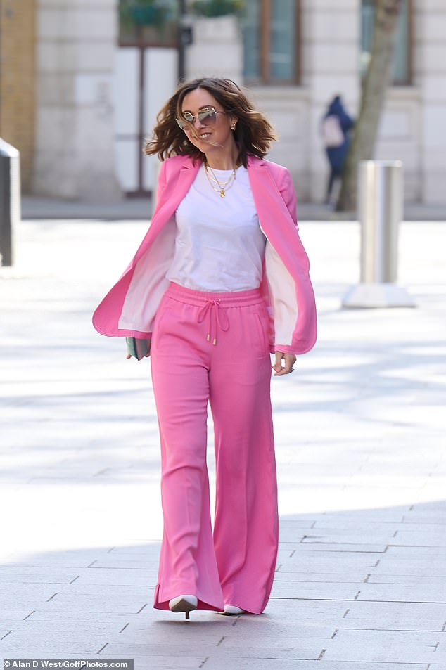Loving life! The presenter wore a white T-shirt underneath her pink suit and completed the look with white heels