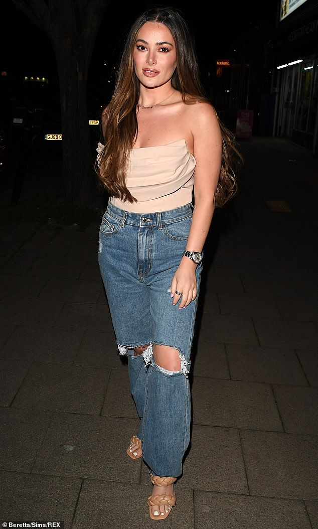 Decolletage: Amber's other friend Courtney Green, 25, put on an effortlessly stylish display in distressed jeans and a sculpted strapless top in a beige hue