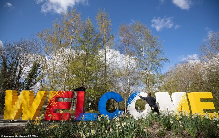 Legoland model makers Elliott Ayton-Smith (left) and Nicola Parker (right) clean and add bricks to a welcome sign at the park