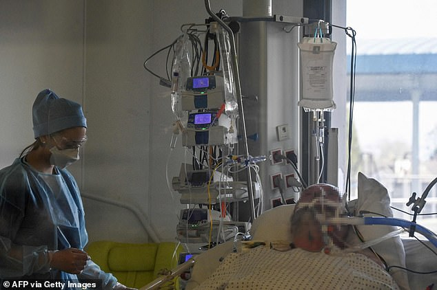 A nurse is seen through a window in the room of a Covid-19 patient under respiratory assistance at the intensive care unit at Valenciennes Hospital on Tuesday