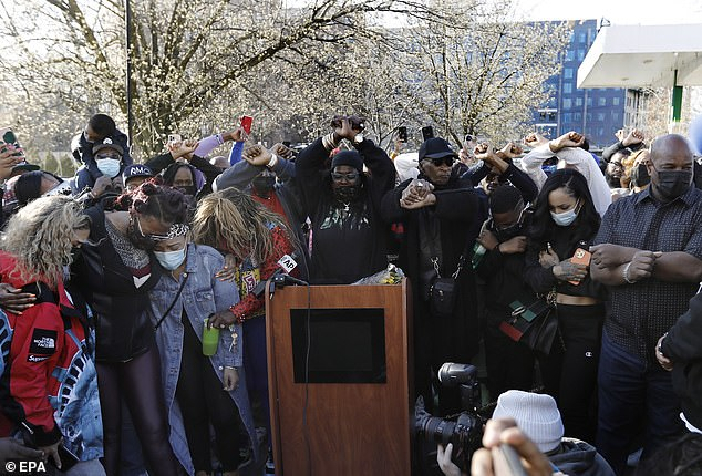 Solidarity: DMX's family, friends and fans raise their arms in an 'X' at the vigil Monday to pay tribute to the rapper who is in ICU