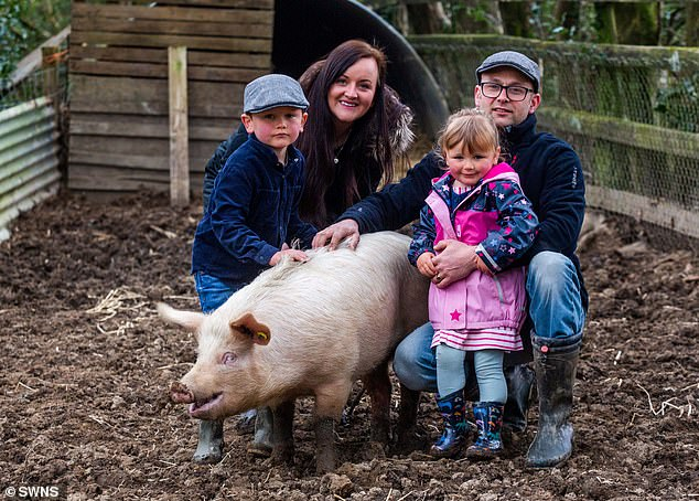 Sarah Allan and her husband Stuart with their children Archie aged six and Phoebe aged three, with their pet pig Milton at their farm near Holsworthy, Devon