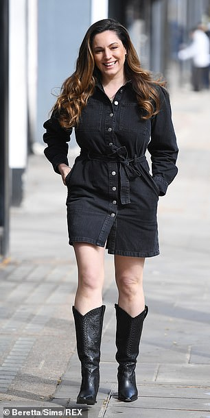 Leggy:She teamed the stylish number with statement black leather cowboy boots as she strutted her stuff along the pavement