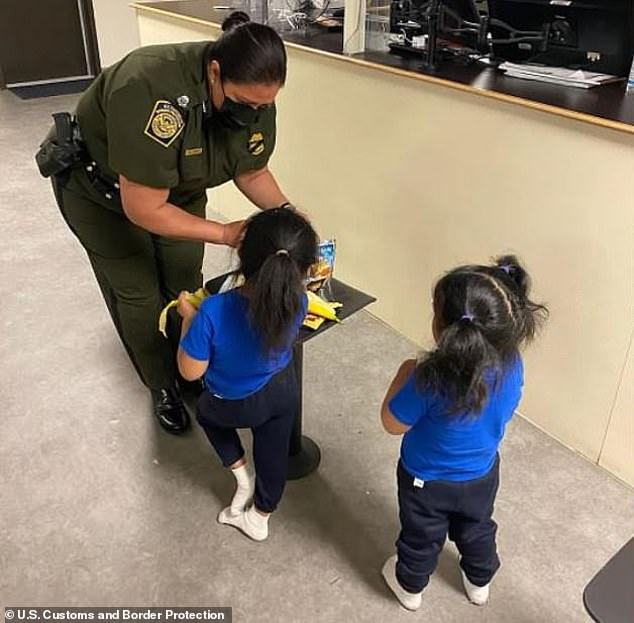 El Paso Sector Chief Patrol Agent Gloria Chavez provides snacks to the two girls from Ecuador who were abandoned by human smugglers and dropped over a 14-foot high border wall in New Mexico last Tuesday. An official with the Consulate of Ecuador in Houston told DailyMail.com on Wednesday that the children will be reunited with their parents, who reside in New York