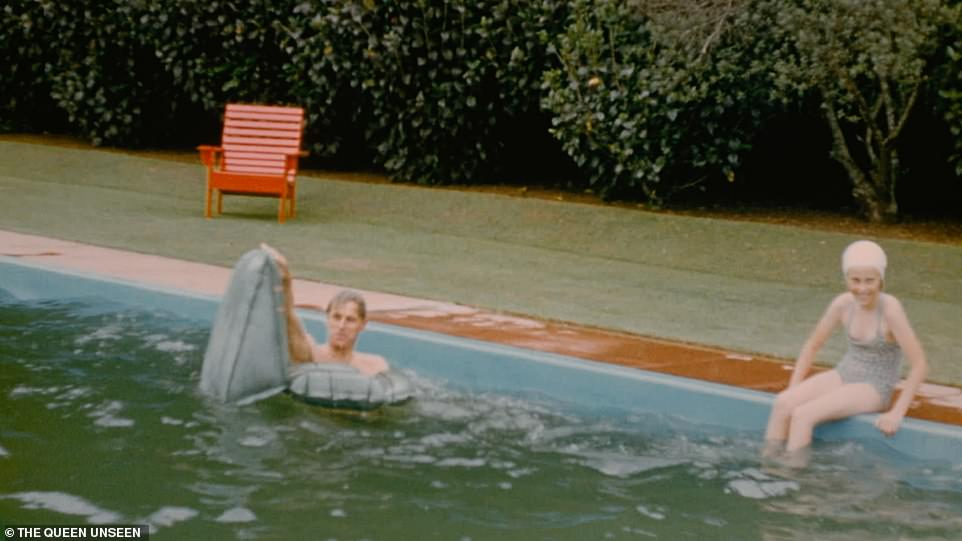 The Duke of Edinburgh struggles to climb onto a lilo in the water with a ten-year-old Sarah Stephenson laughing as she sits by the pool on Christmas Day 1953 while the royal couple take a break from their gruelling seven-month Commonwealth tour