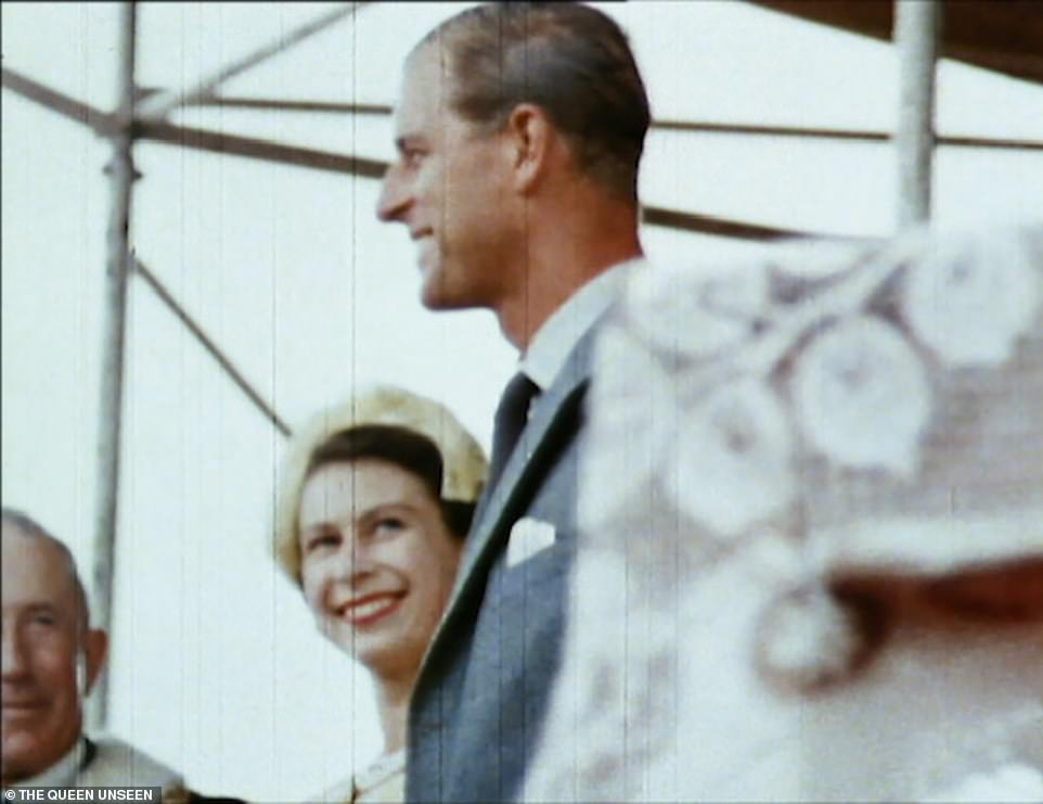 The Queen and Prince Philip in New Zealand in 1953. She is seen smiling at him, while talking to one of the dignitaries at an engagement during their tour of the country which saw them stay there during Christmas that year