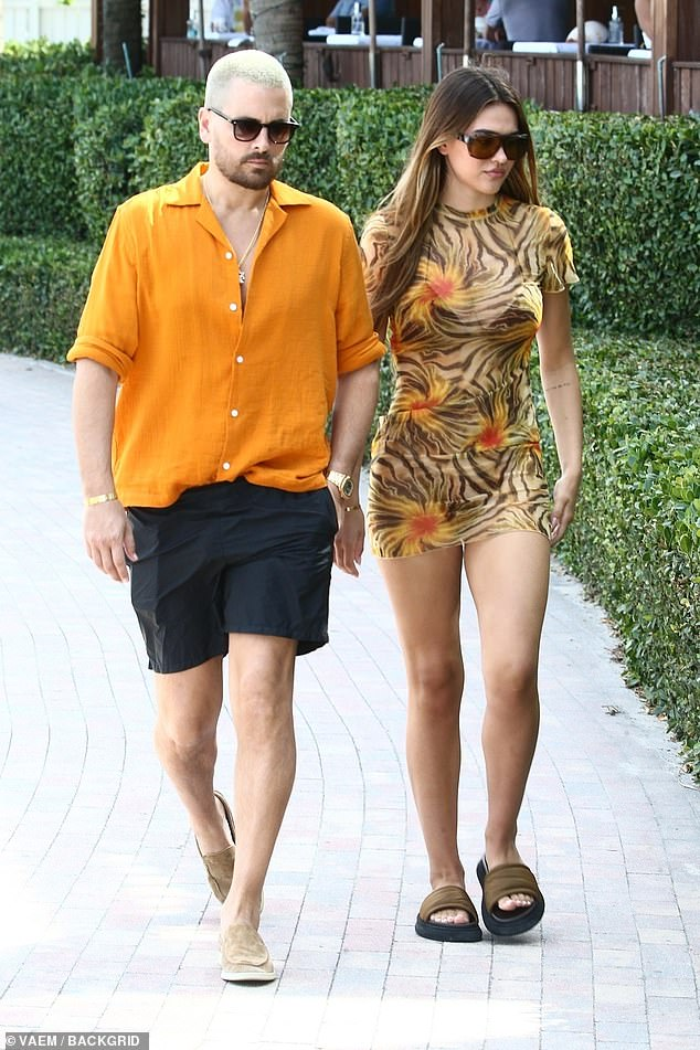 Blessed: The 19-year-old budding supermodel rocked a sheer floral bikini cover-up to match his electric orange shirt as they made their way back to the hotel while on Spring Break together in South Beach
