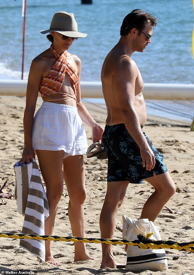 Back on shore:After enjoying a dip in the ocean, Rachael returned to the shore and covered up from the sun in a grey fedora and sunglasses. Pictured with husband Michael Miziner