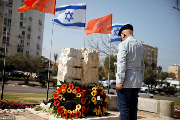 A man stands at a memorial in-front of two wreaths as a two-minute siren marking the annual Israeli Holocaust Remembrance Day is heard in Ashkelon, Israel April 8, 2021. As a place of refuge for Jews across the world, hundreds of thousands of Holocaust survivors who had lost their homes and families fled there
