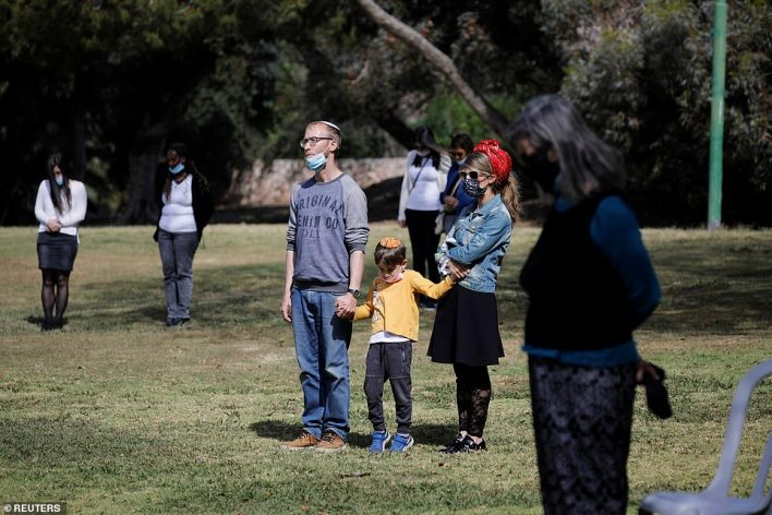 People stand still as a two-minute siren marking the annual Israeli Holocaust Remembrance Day is heard in Ashkelon, Israel April 8, 2021