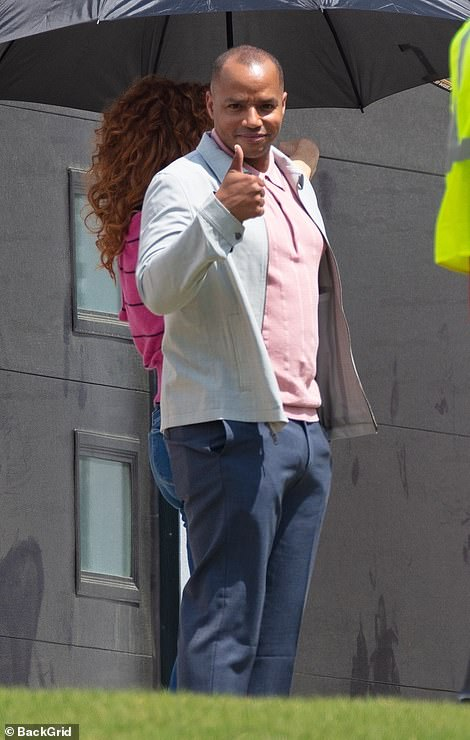 Casual: He looked casual yet stylish in a muted gray jacket with a pink striped polo shirt and gray–blue pants
