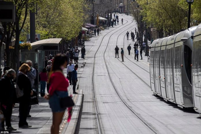 Israelis observe a moment of silence in central Jerusalem along tram tracks as sirens sound throughout the country to mark Holocaust Remembrance Day in Jerusalem, Israel, 08 April 2021