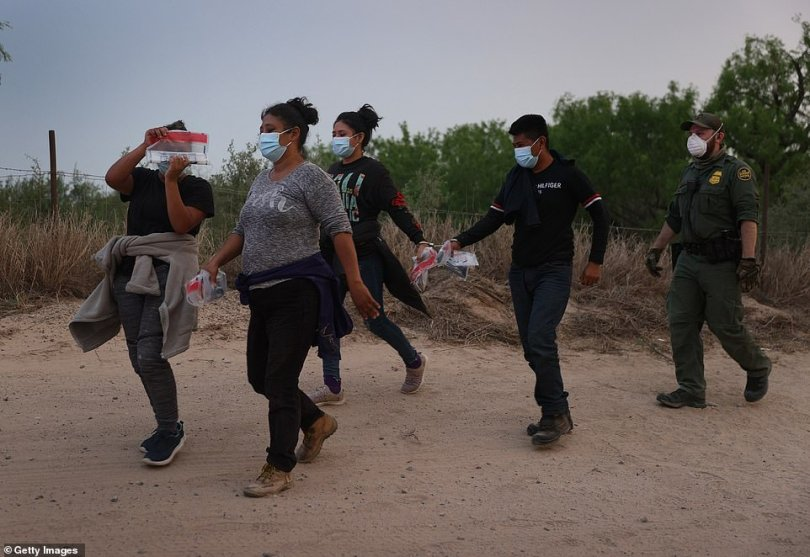 A group of migrants is detained by the Border Patrol in Penitas, Texas, on March 27