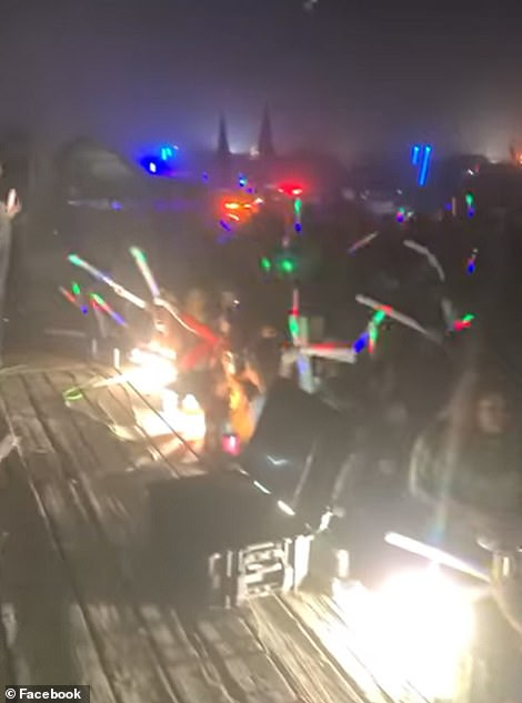 Revelers are seen holding up glow sticks during the party